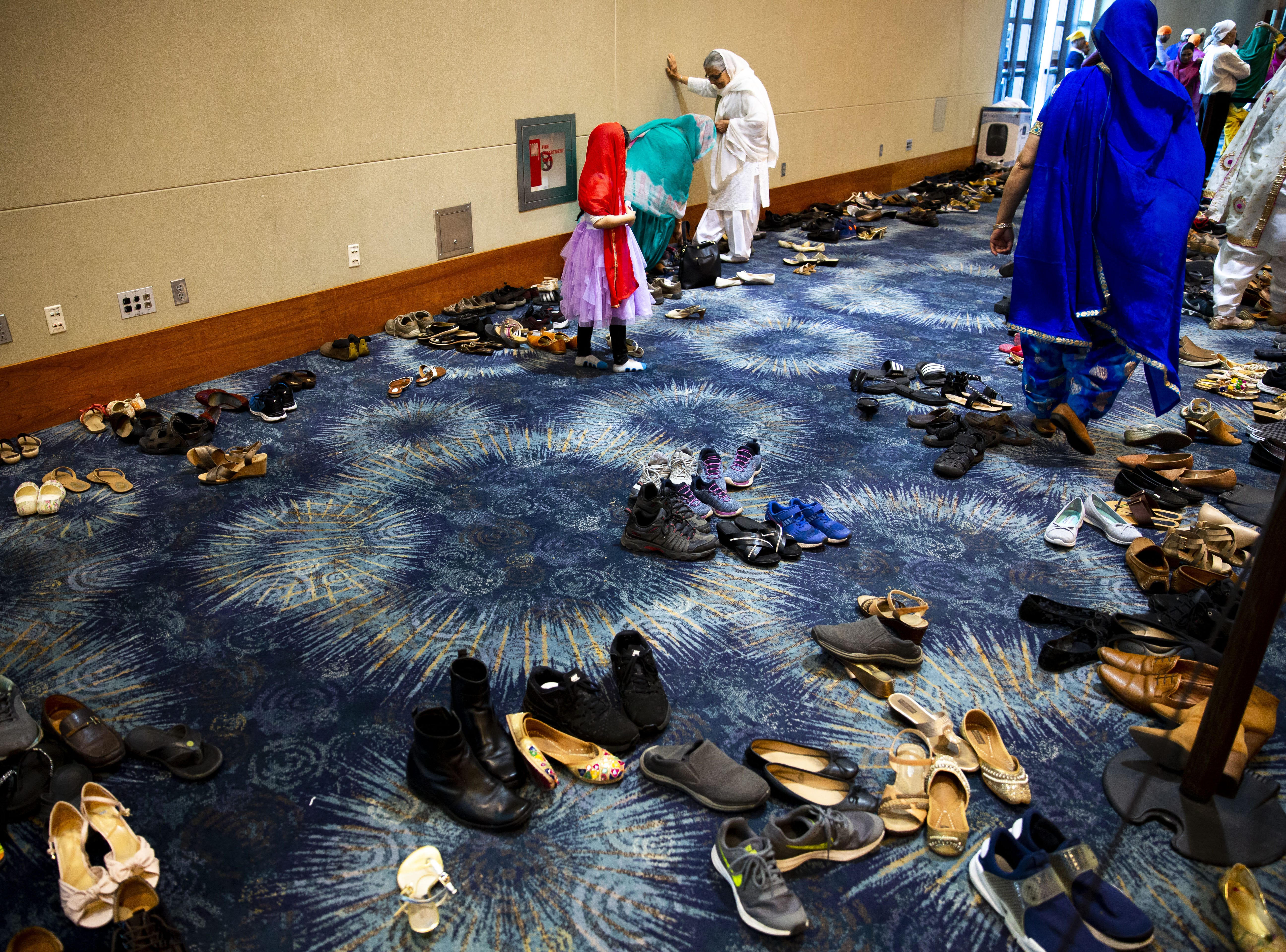 People take off their shoes to pray at the Phoenix Convention Center on March 24, 2019.