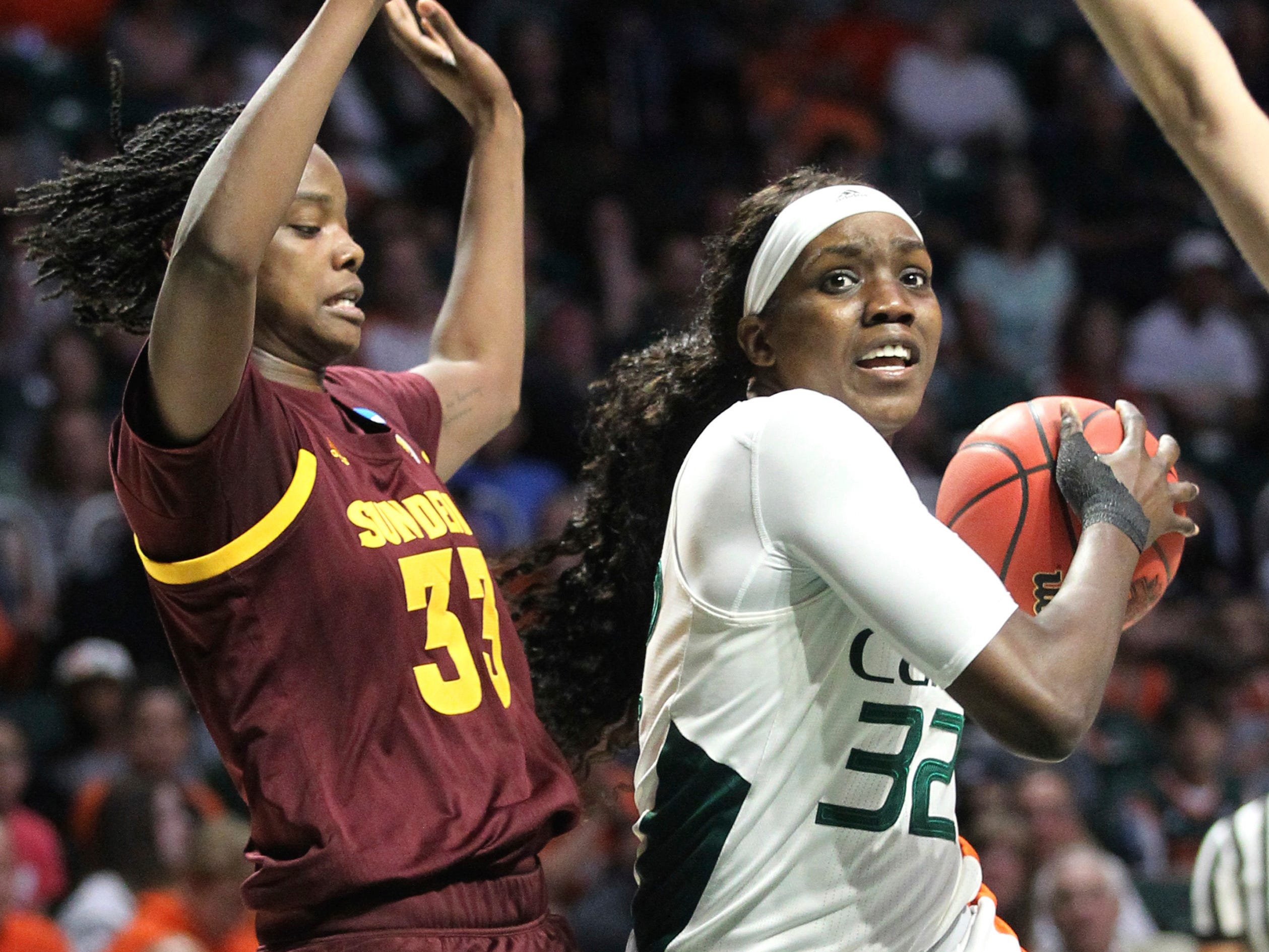 Miami's Beatrice Mompremier (32) moves the ball on Arizona State's Charnea Johnson-Chapman, left, during a second-round women's college basketball game in the NCAA Tournament, Sunday, March 24, 2019, in Coral Gables, Fla. (AP Photo/Luis M. Alvarez)