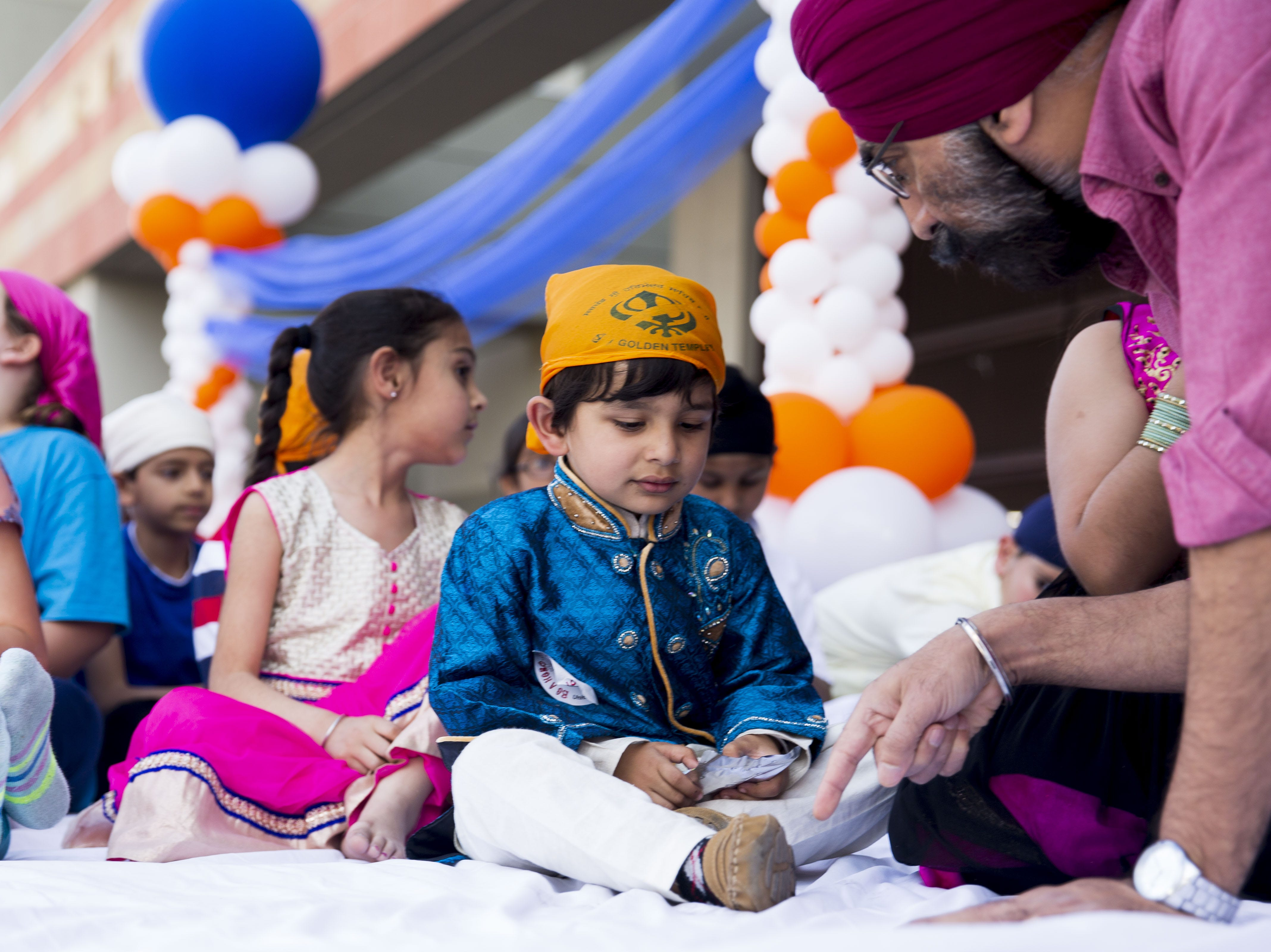 Agam Bajwa, 3, sits on the float as he waits for the Sikh parade in Phoenix to begin on March 24, 2019.