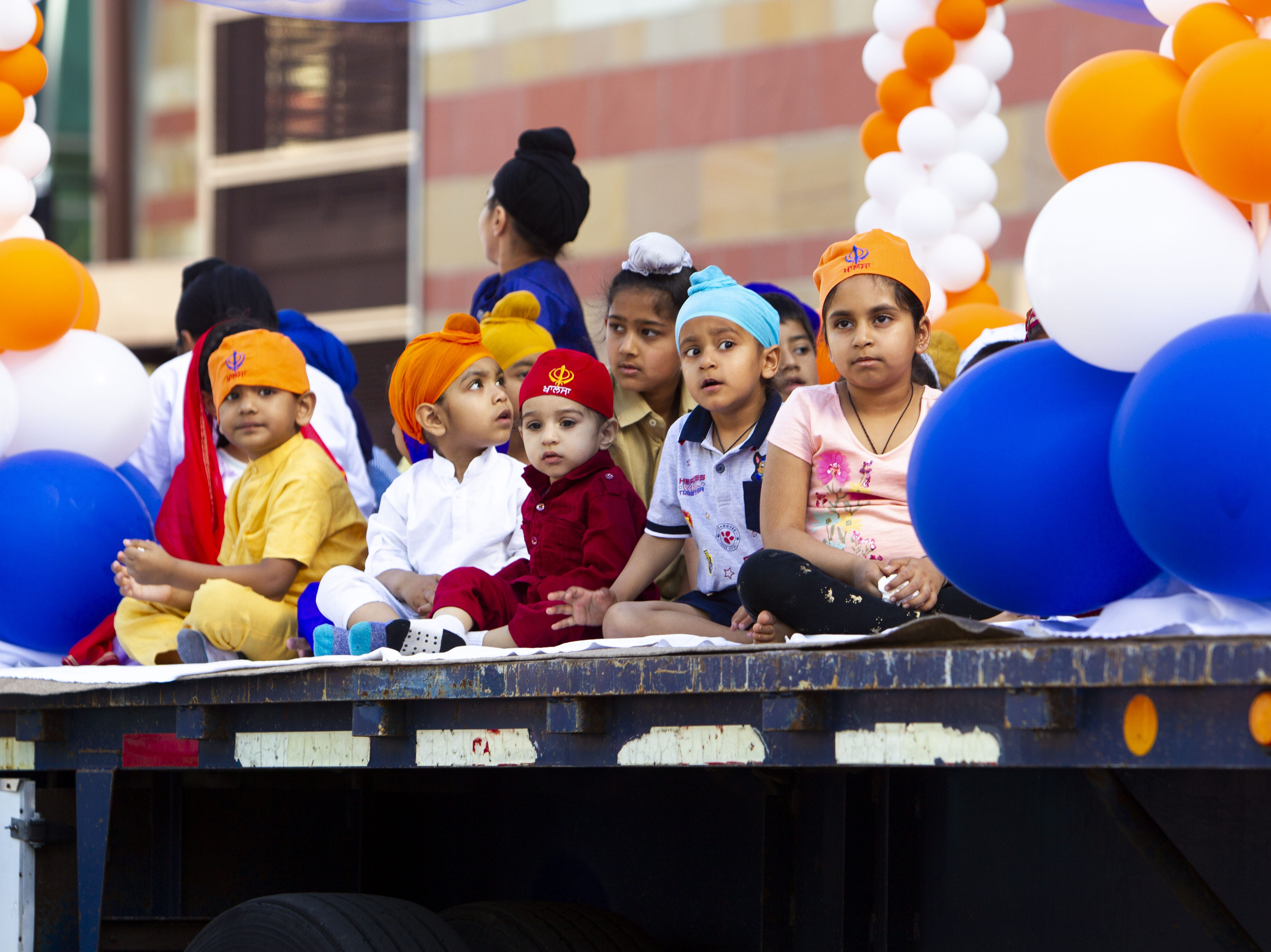 Children sit on a float during a Nagar Kirtan procession in downtown Phoenix on March 24, 2019.