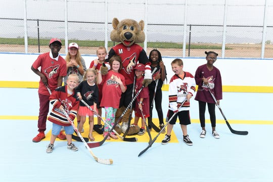 Arizona Coyotes mascot Howler poses with Arizona Coyotes and Tucson Roadrunner ball hockey participants.