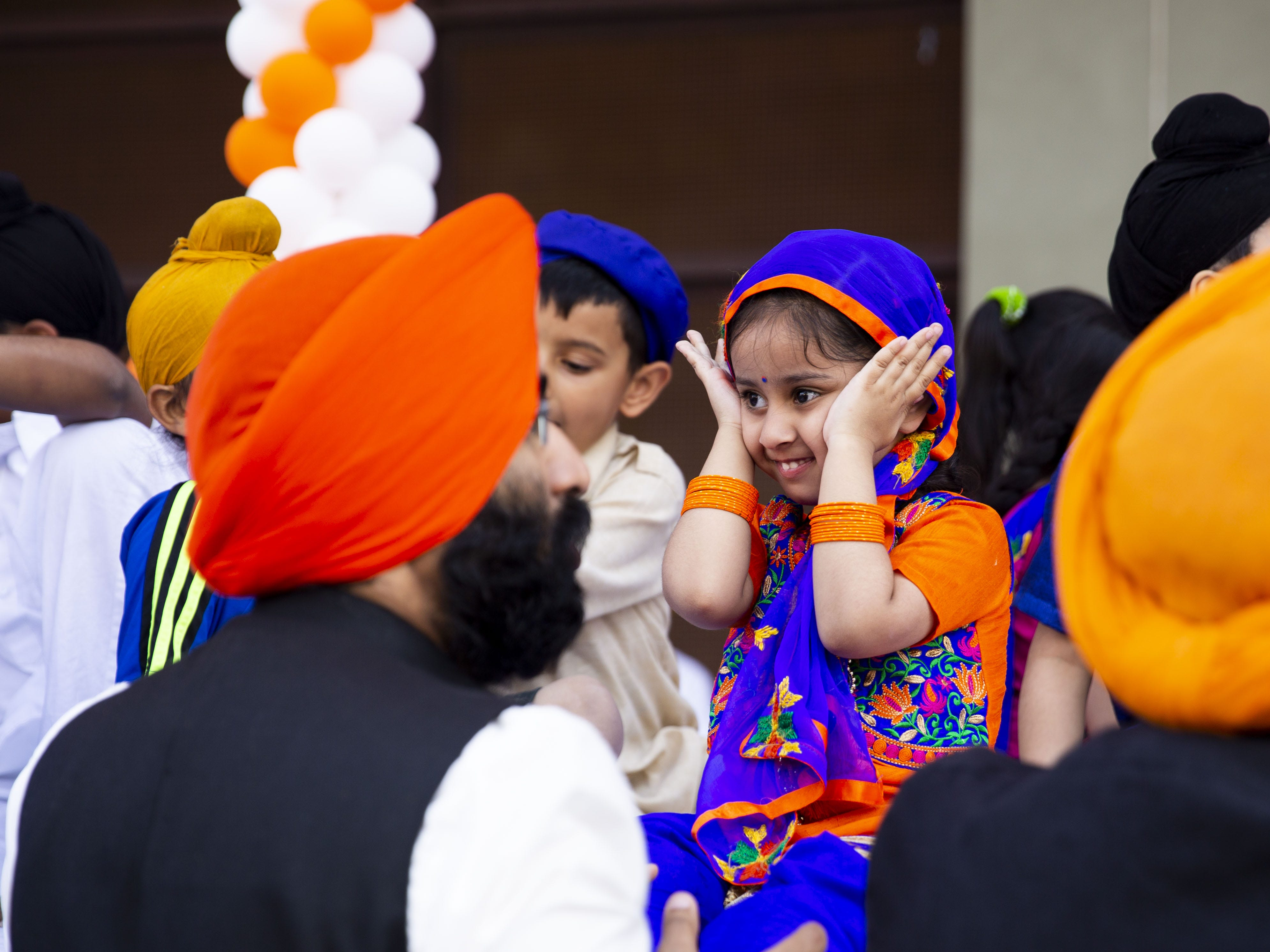Harleen Kaur, 3, plays peek-a-boo with her father as they wait for the parade to start on March 24, 2019.
