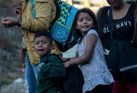 Niños que acompañan a un grupo de inmigrantes centroamericanos a través de la frontera lloran al brincar la valla en Tijuana.