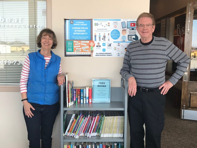 Lynne Kroeger, president of the Friends of Ida Rupp Public Library, and Friends member John Gibson stand next to the free book cart recently placed right outside the door of Bistro 163.