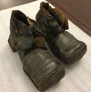 Century old hobo boots worn by a York man show how patches of leather were nailed to the well-worn footwear. The left boot weighs 8 pounds, 5 ounces; the right one 9 pounds, 8 ounces.