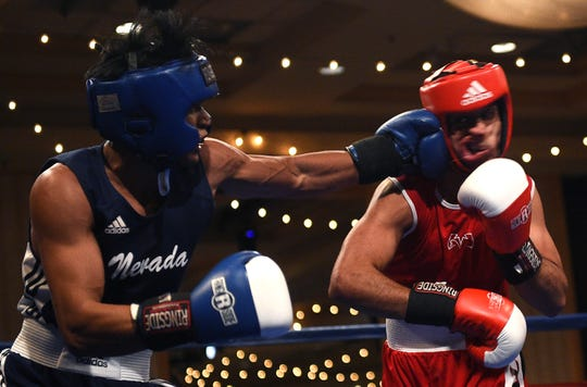 Nevada's JJ Mariano, left, connects against UNLV's Mike Alvarez during their 147 pound bout at the  NCBA Western Regional Championships  at the Eldorado Hotel Casino in Reno on March 25, 2016.