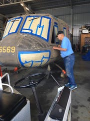 """Joe Goebel, president of the Wayne County Veterans Memorial Park Committee, examines aUH-1 """"Huey"""" helicopter to Richmond that will be displayed at Veterans Memorial Park."""