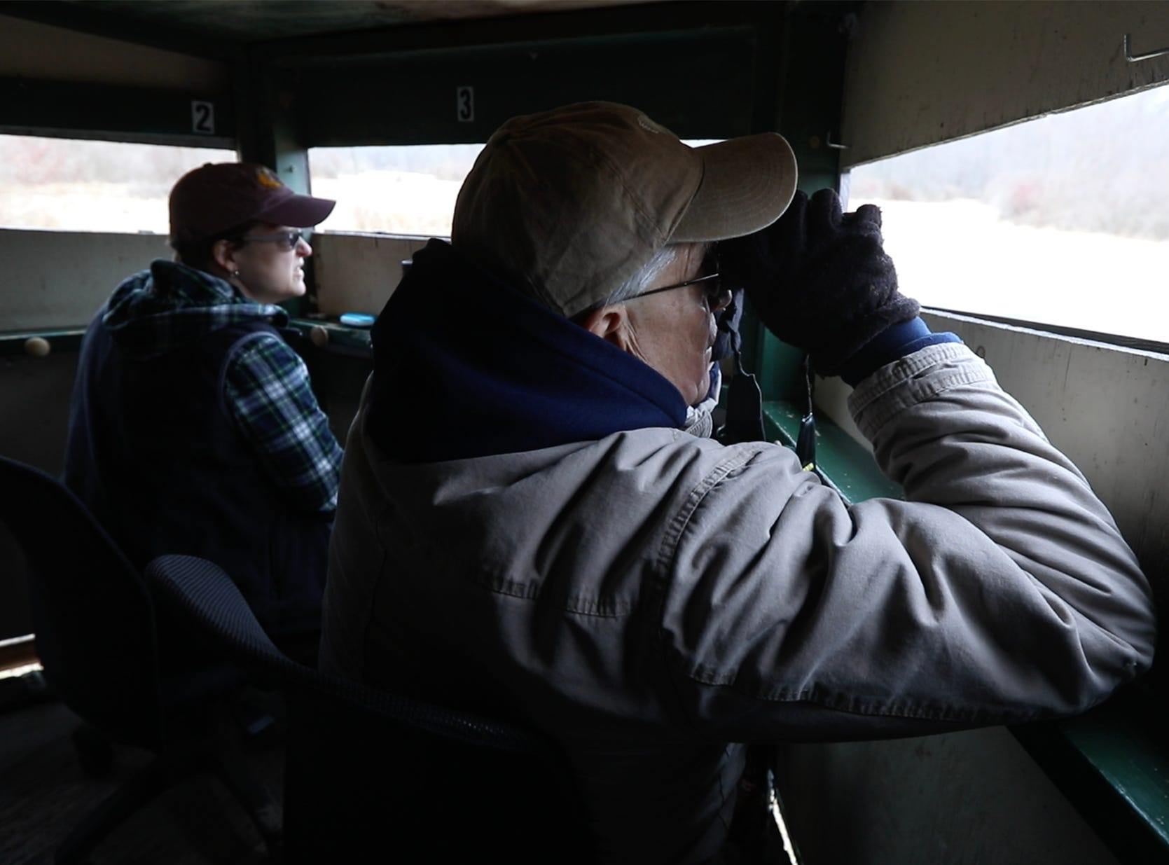 Barb French and Jim Saller look off to see if a hawk has entered the area.