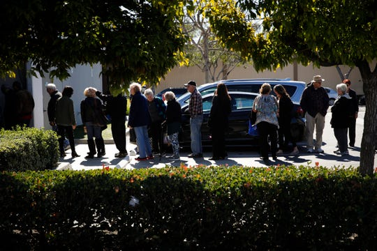 A group of retired seniors from Laguna Woods Village form a line outside Bud and Bloom cannabis dispensary to attend a presentation organized by cannabis product vendors in Santa Ana, Calif.