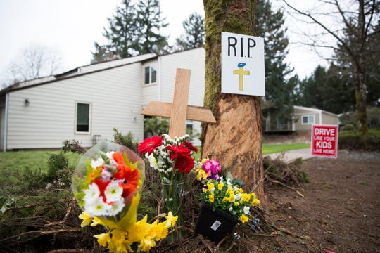 Flowers and a cross are placed by a tree where one teen died and four others were injured in a car crash on the 6600 block of Fairway Avenue SE. on March 25, 2019. The crash took place on March 23 around 4 a.m.