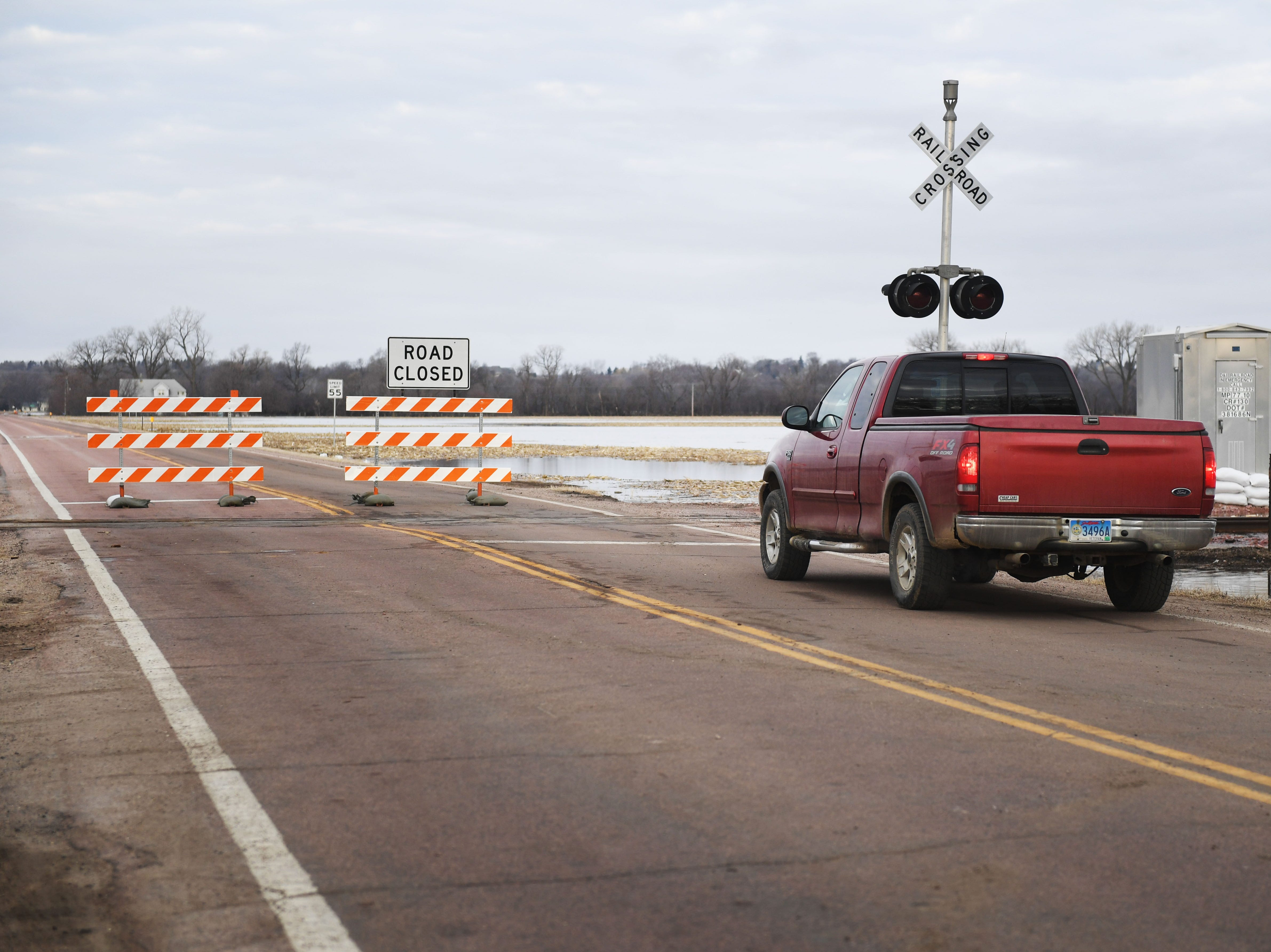 "A motorist sits in their car at the ""road closed"" sign in Renner Monday, March 25, in Renner, S.D. The road was closed because of flooding over the street."
