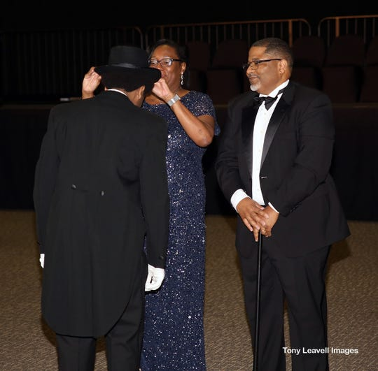 Reggie Grant and  Adriane Glenn Grant present their son Micah with his Links Beautillion top hat and cane.