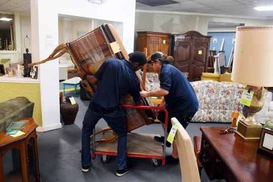 "Charles Crist (left) and Tyler Luce carefully load an antique cabinet onto a trolly on Monday, March 25, 2019, after the piece was sold at the Habitat for Humanity ReStore in Jensen Beach. Second-hand and thrift stores across the Treasure Coast have seen an increase in donations the fist two months of the year following the debut of ""Tidying Up with Marie Kondo,"" a show on Netflix where families are guided through the process of decluttering their homes."