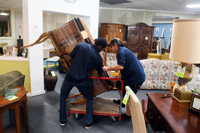 """Charles Crist (left) and Tyler Luce carefully load an antique cabinet onto a trolly on Monday, March 25, 2019, after the piece was sold at the Habitat for Humanity ReStore in Jensen Beach. Second-hand and thrift stores across the Treasure Coast have seen an increase in donations the fist two months of the year following the debut of """"Tidying Up with Marie Kondo,"""" a show on Netflix where families are guided through the process of decluttering their homes."""
