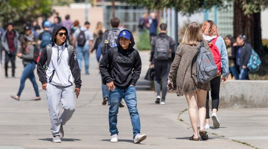 "Students Armando Santillan, left, and Christian Mendoza traverse the College of the Sequoias campus on Monday, March 25, 2019. Enrollment of VUSD students at COS has climbed more than 20% since 2014 to 775 for the fall semester. VUSD and COS offer dual-enrollment and concurrent classes to help students gain college credit while also meeting requirements to graduate from high school. The programs are beneficial to help ""bridge the cap"" from high school to college, according to VUSD administrators."