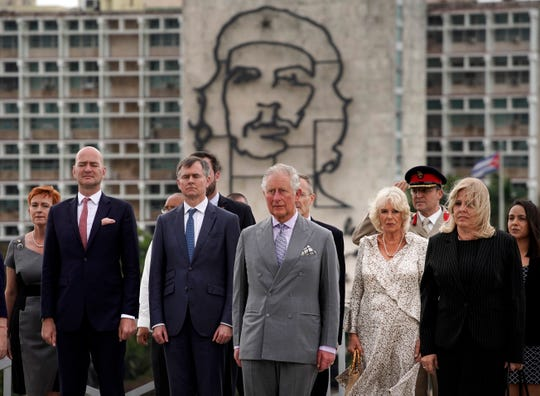 Backdropped by an image of Che Guevara, Britain's Prince Charles, the Prince of Wales, center, and Camilla, Duchess of Cornwall, center right, attend a wreath-laying ceremony at the Jose Marti Monument during their official visit in Havana, Cuba, Sunday, March 24, 2019. (AP Photo/Ramon Espinosa) ORG XMIT: XRE101