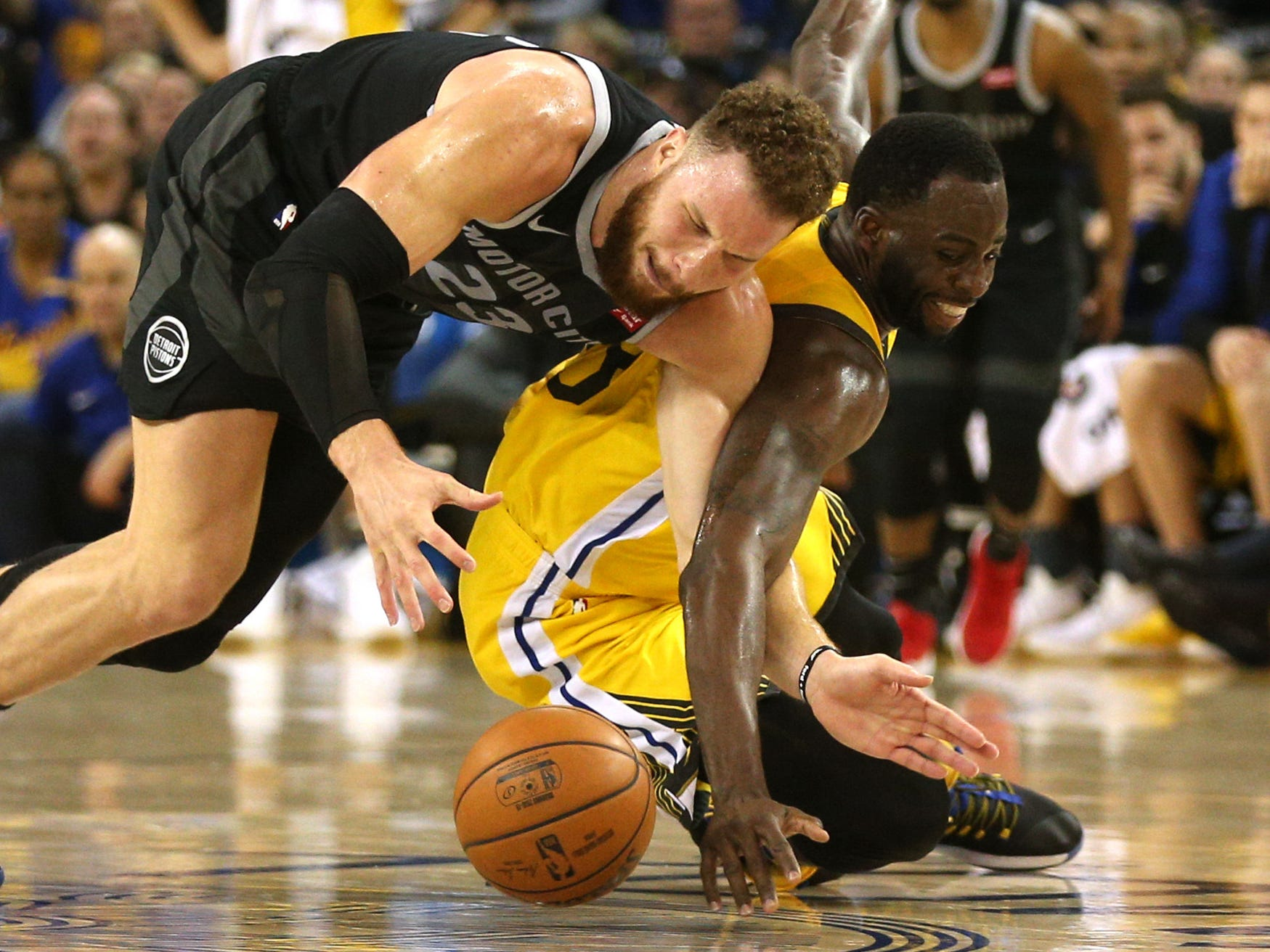 March 24: Pistons forward Blake Griffin and Warriors forward Draymond Green scramble for a loose ball during the second half in Oakland.