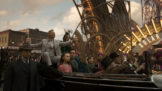 "Famous businessman V.A. Vandevere (Michael Keaton, in gray) shows off his larger-than-life amusement park Dreamland in ""Dumbo."""