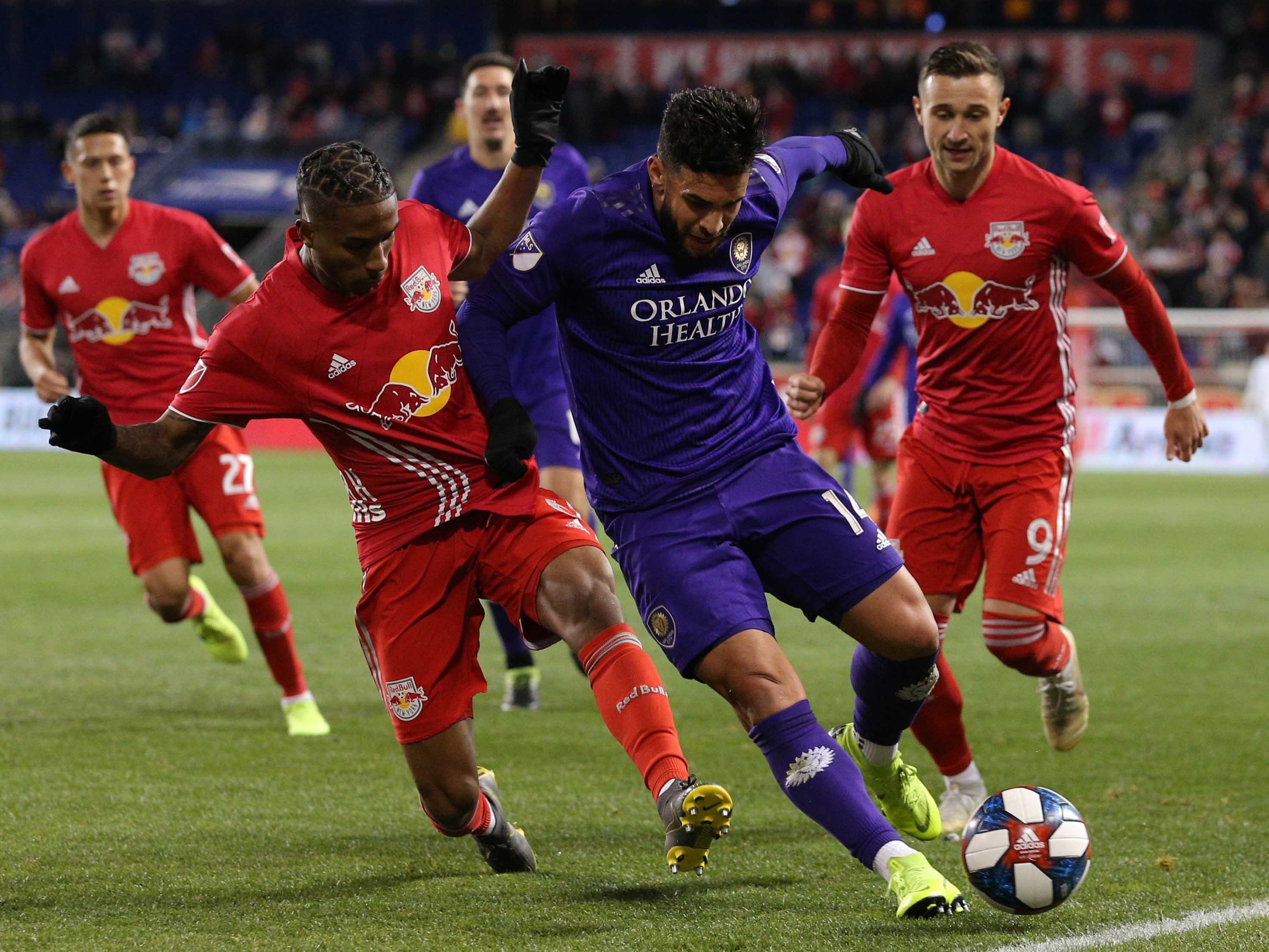 March 23: Orlando City SC forward Dom Dwyer plays the ball against New York Red Bulls defender Kyle Duncan and forward Andreas Ivan (9) during the second half at Red Bull Arena. Orlando won the game, 1-0.