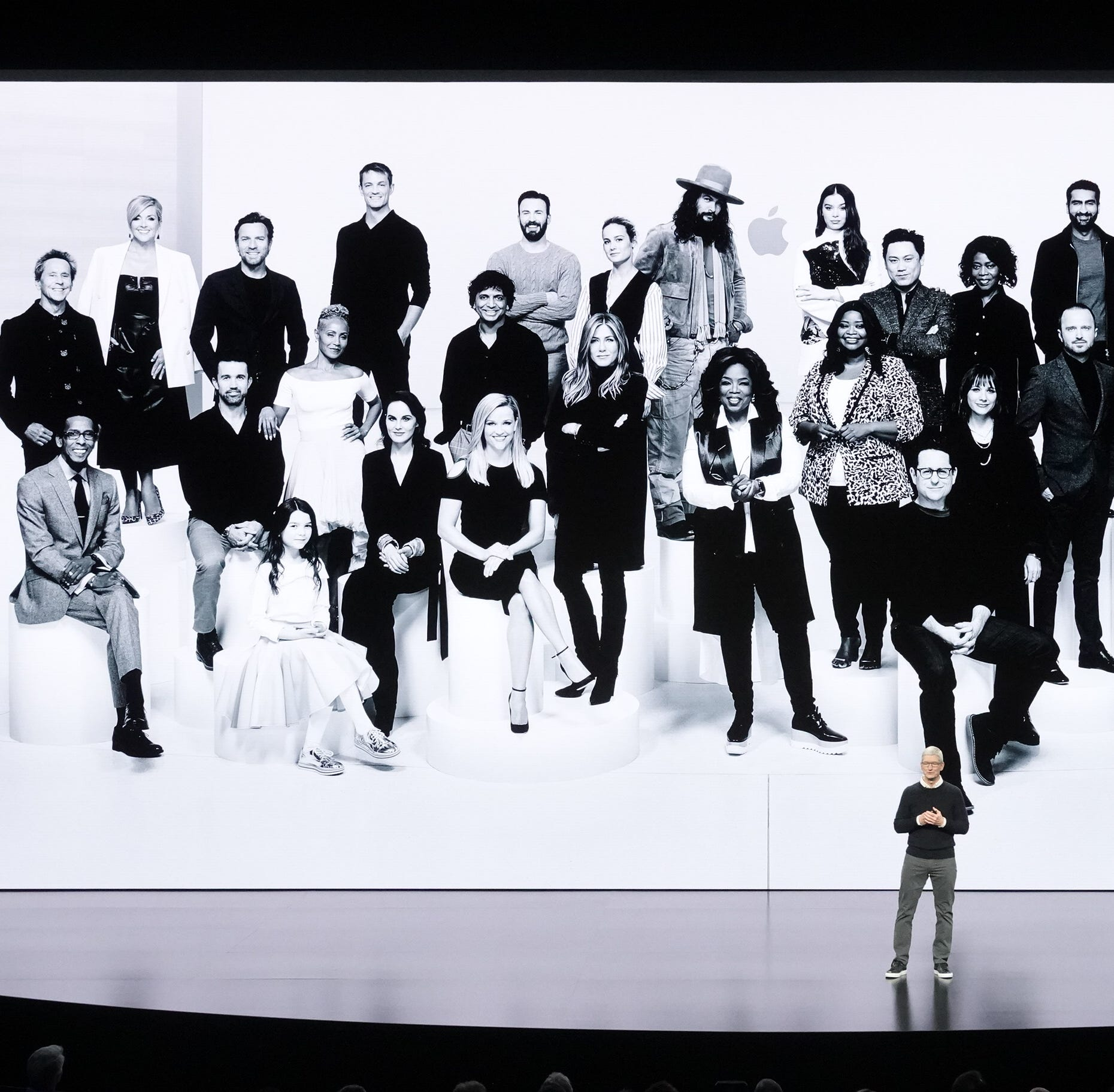 Apple CEO Tim Cook at event announcing TV+ subscription service, in front of group photo of Apple stars, including Oprah Winfrey, Reese Witherspoon and others
