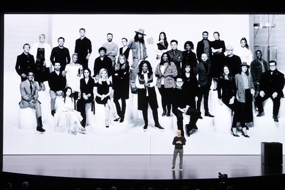 Apple CEO Tim Cook at event announcing TV+ subscription service, in front of group photo of Apple stars, including Oprah Winfrey, Reese Witherspoon and others.