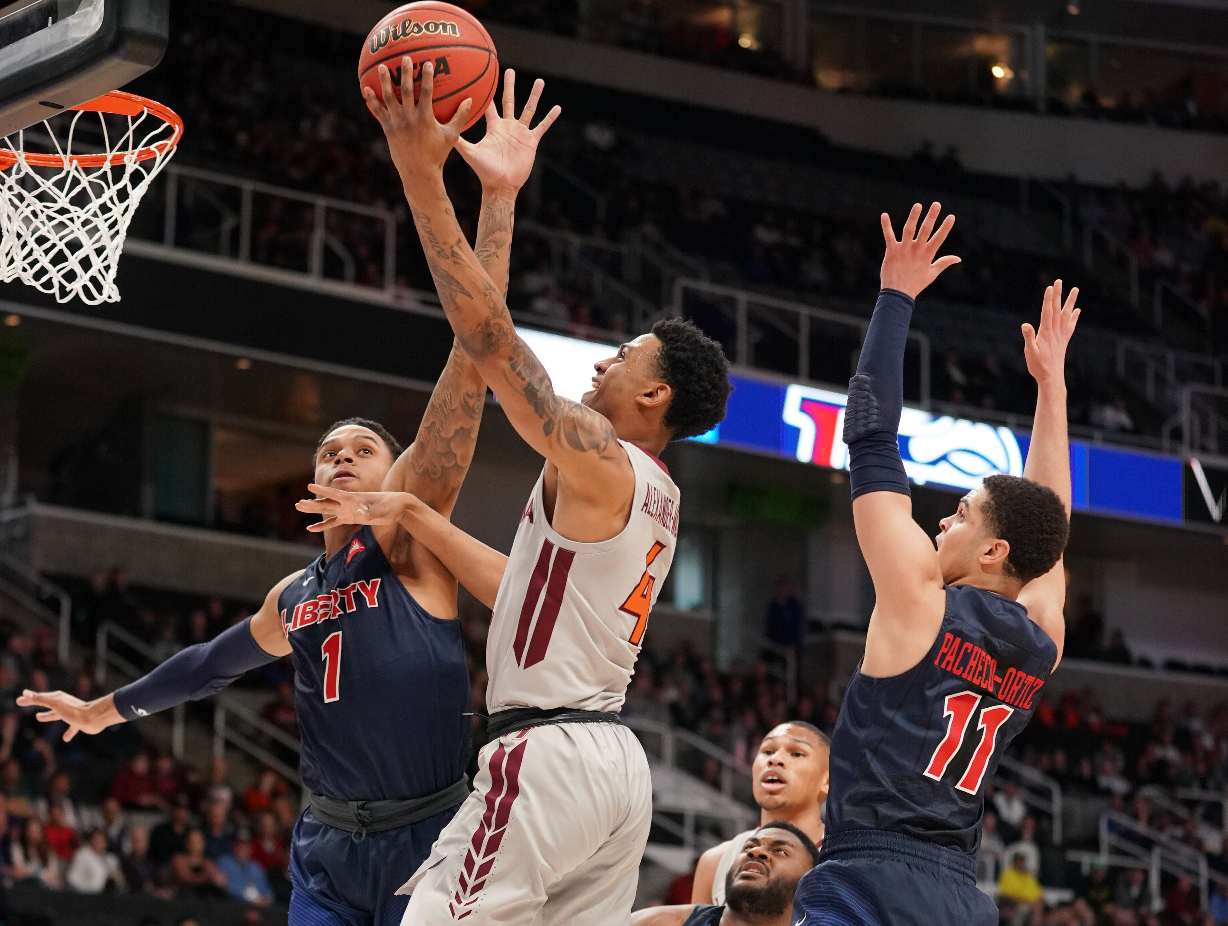 Round of 32: Virginia Tech guard Nickeil Alexander-Walker (4) shoots between Liberty guards Caleb Homesley (1) and Georgie Pacheco-Ortiz (11) during the first half.