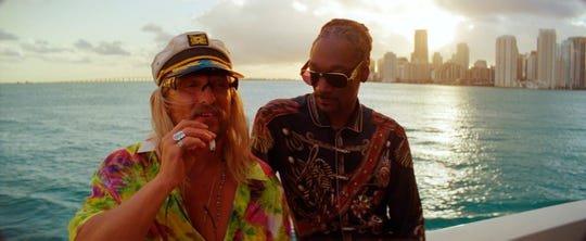 "Moondog (Matthew McConaughey, left) and Lingerie (Snoop Dogg) enjoy a smoke on the water in ""The Beach Bum."""