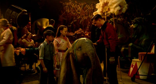 "Holt Farrier (Colin Farrell, right) and his children Joe (Finley Hobbins) and Milly (Nico Parker) become caretakers for a flying baby elephant in Tim Burton's ""Dumbo."""