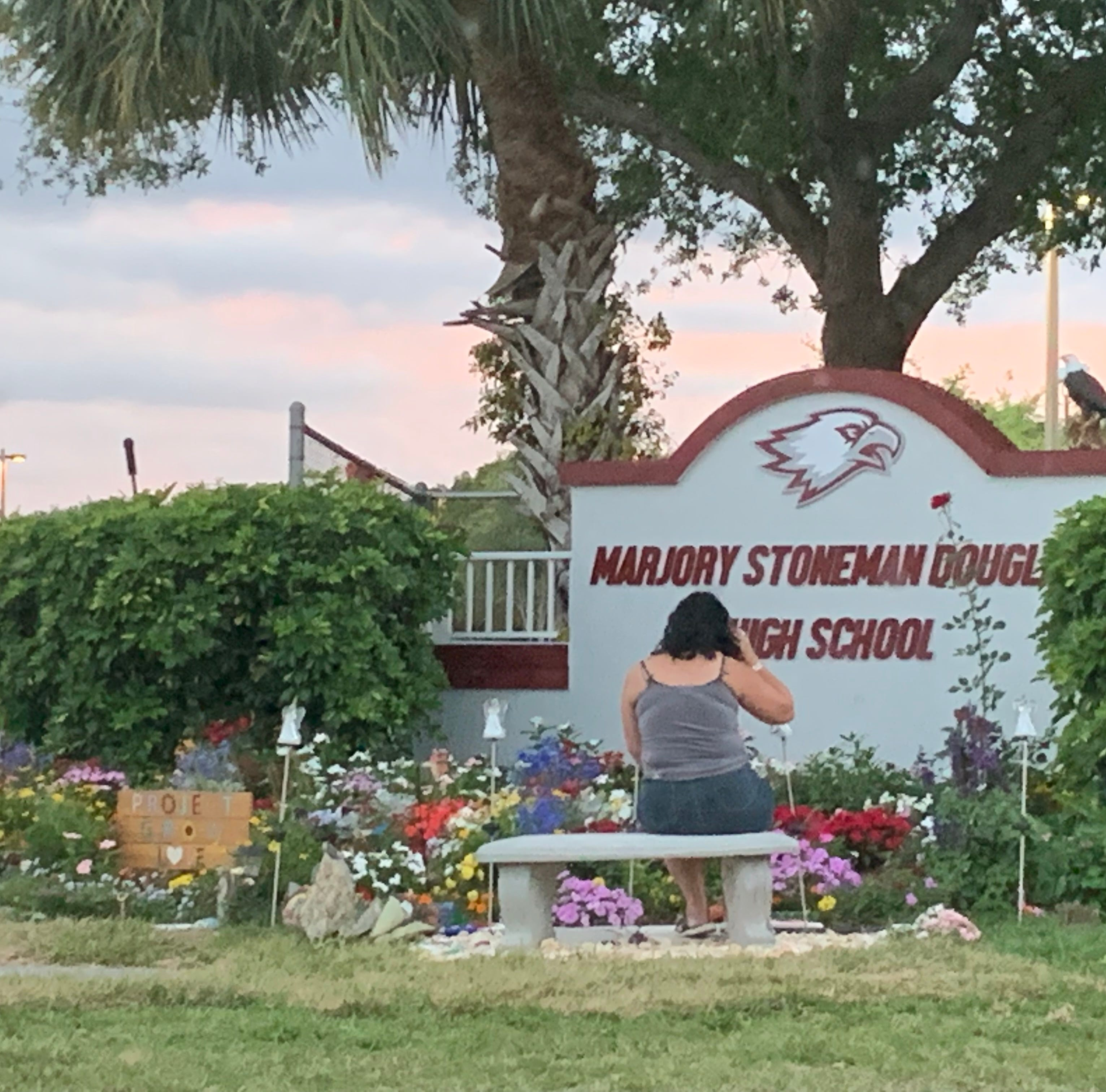 A woman sits Sunday at a sign for Marjory Stoneman Douglas High School in Parkland, Florida.