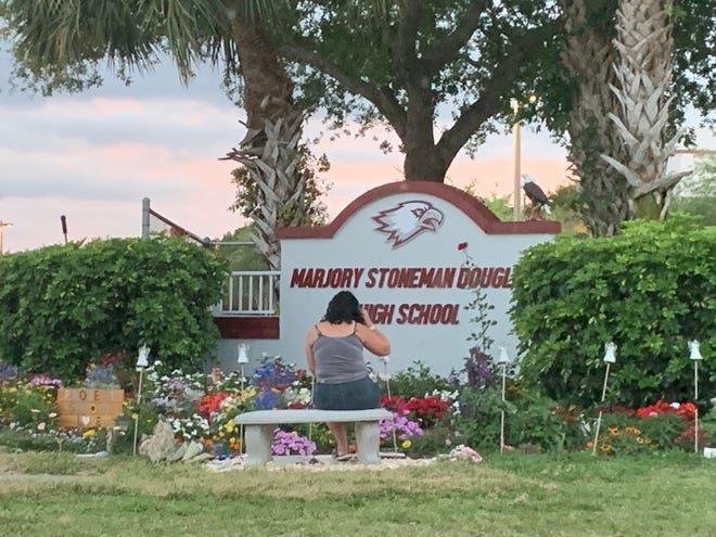 A woman sits at a sign for Marjory Stoneman Douglas High School in Parkland, Florida.