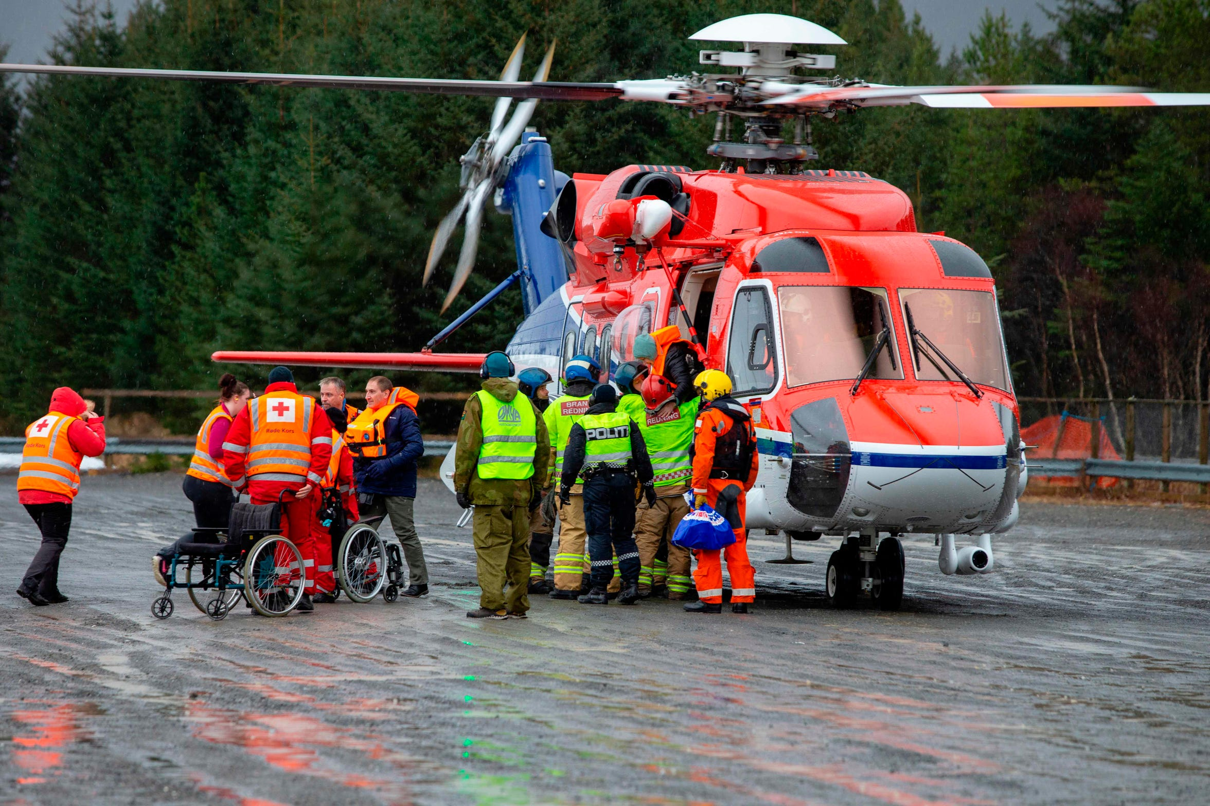Rescuers wait to assist passengers airlifted by helicopter from the cruise ship Viking Sky on March 24, 2019 off the west coast of Norway.