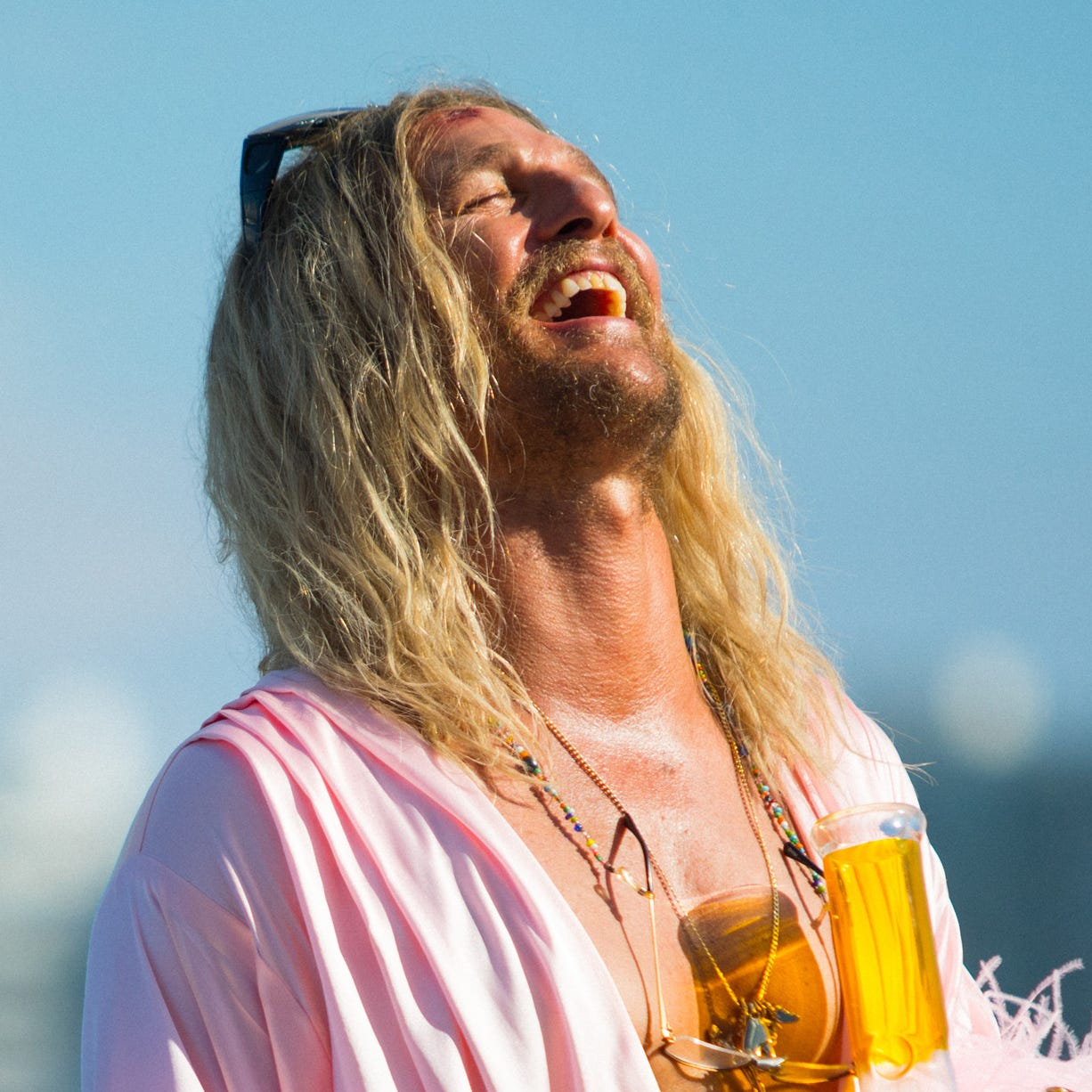 "As Moondog, Matthew McConaughey wears women's clothing and enjoys an adult beverage in the stoner comedy ""The Beach Bum."""