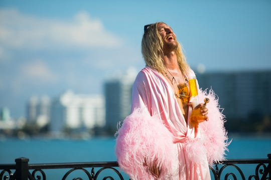 """As Moondog, Matthew McConaughey wears women's clothing and enjoys an adult beverage in the stoner comedy """"The Beach Bum."""""""