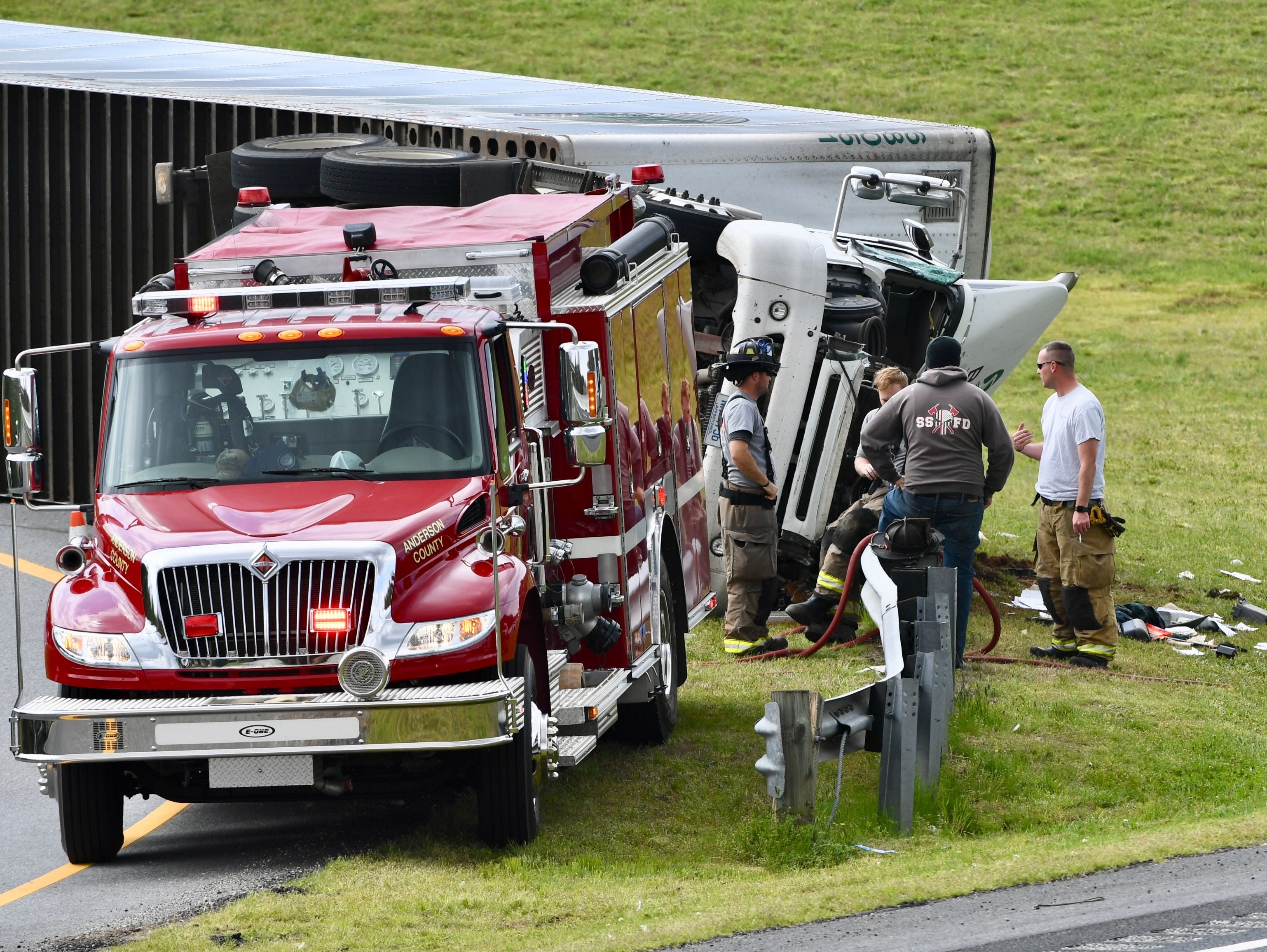Townville fire department personnel at the scene of an overturned 18-wheeler truck on the northbound Interstate 85 on-ramp at Exit 19 on Tuesday, March 26, 2019.