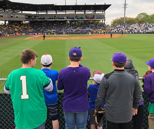 Boys gather along the right-field railing at LSU's Alex Box Stadium, waiting for Tiger right fielder Antoine Duplantis to toss them a ball. Whoever catches the ball signs their name on it and tosses it back to Duplantis at the start of the next inning.