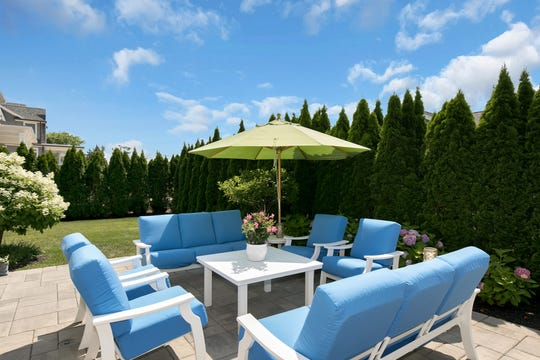 The backyard features stone patio and lavish greenery.