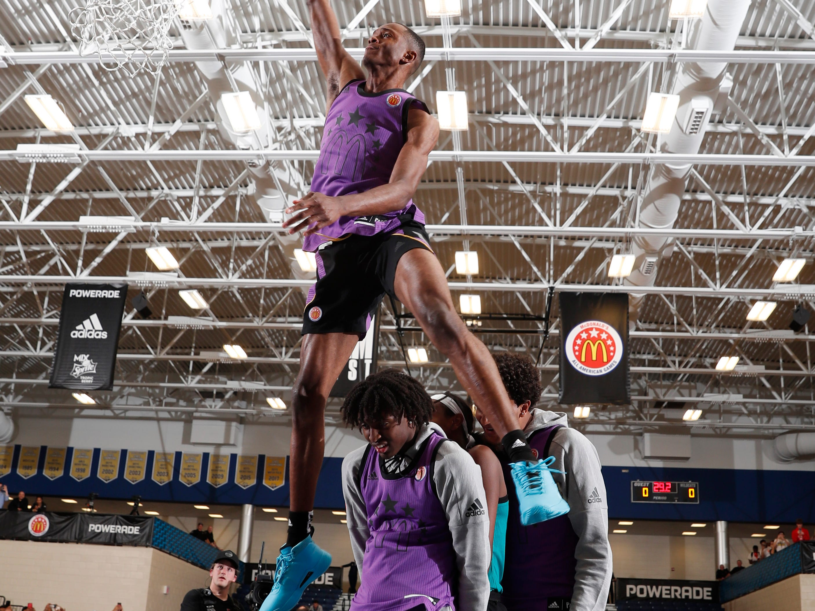 Mar 25, 2019; Marietta, GA, USA; McDonalds High School All American forward Scottie Lewis jumps over two players as he dunks during the Powerade Jamfest dunk competition at Wheeler High School. Mandatory Credit: Brian Spurlock-USA TODAY Sports