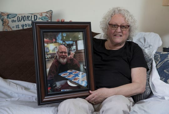 Toms River resident Alice Seccafico sits in her living room with a photo of her late husband John Seccafico.
