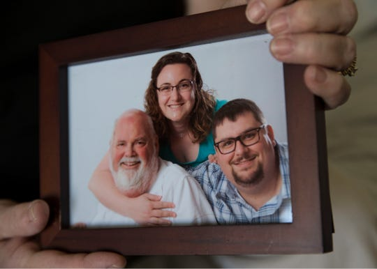 Toms River resident Alice Seccafico sits in her living room with a photo of her late husband John Seccafico and children Sarah Harper and Robert Connelly.