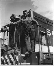 James Waters, a hostler at Southern Railroad's roundhouse, poses with one of the engines he maintained in the 1950s.