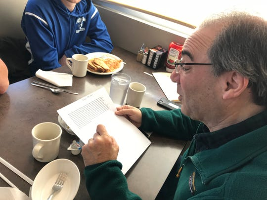 Retired Maine-Endwell High School teacher John Perricone reads a message he plans to post on Facebook, announcing the 999th and 1000th breakfast he's shared with a former student.