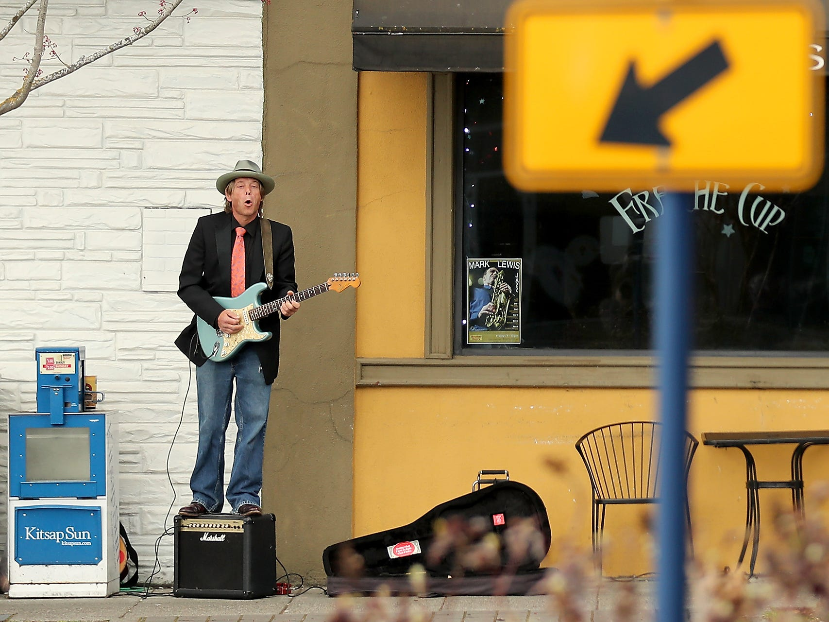Musician Kenny Wayne Gunner, of Seattle, stands on top of his amp as he plays his electric guitar on the sidewalk in front of Fraiche Cup in downtown Bremerton on Tuesday, March 26, 2019.