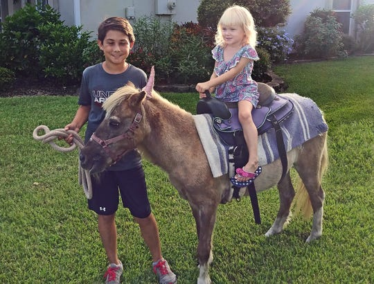 Thirteen-year-old Luke Diaz of Malabar, poses for a picture with his sister Grace, 4, on trusty steed Cupcake from King Party Rental. Cupcake will be giving rides during Advent Lutheran Church's free Family Fun Day on April 6 in Melbourne Beach.