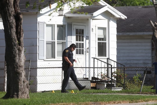A Corpus Christi police officer walks around two evidence markers outside a home in the 200 block of Torreon Street on Tuesday, March 26, 2019.