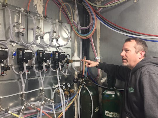Neck of the Woods co-owner and brewer Frank Price checks out the taps system that transports beers from the brewhouse to the tasting room at the new Mantua brewery.