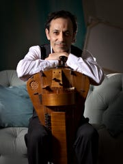 Tomas Lozano with his hurdy-gurdy, a stringed instrument that produces sound by a hand crack-turned, rosined wheel rubbing against the strings, somewhat like a violin bow.
