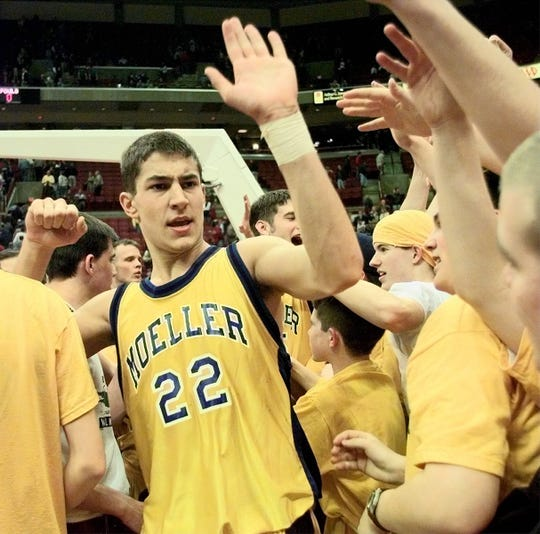 Moeller's Mike Monserez gives high fives as he passes by the Moeller students section after the Crusaders defeated Mansfield 49-43 in the boys Division I semifinal in Columbus. The Crusaders then advanced to play Shakers Heights in the state championship.