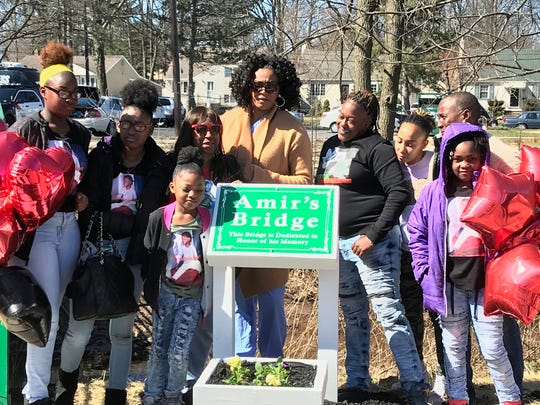 The family of Amir Beeks gathers around the sign for a bridge dedicated Tuesday in his memory next to the Henry Inman Branch Library in the Colonia section of Woodbridge.