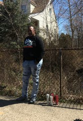 Krystal Singleton stands next to the candles placed in memory of her 3-year-old brother Amir Beeks who was killed by another child in 2003. Amir's body was found in the creek behind the fence on Amherst Avenue.