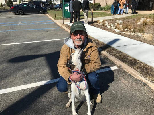Jeff MacBride and his dog Layla attend the dedication of bridge by the Henry Inman Branch Library in Colonia in memory of 3-year-old Amir Beeks.